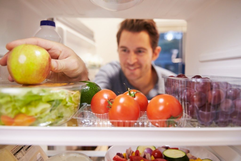 Man picking apple from inside fridge