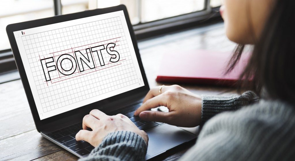 a woman creating font in her laptop