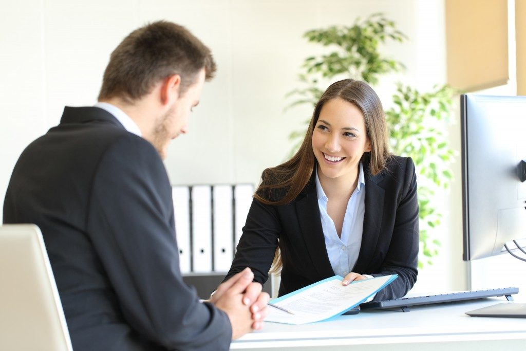 woman asking her client to sign a document