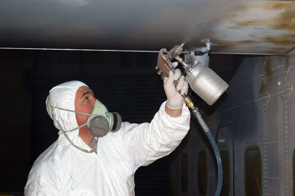 man wearing protective suit painting