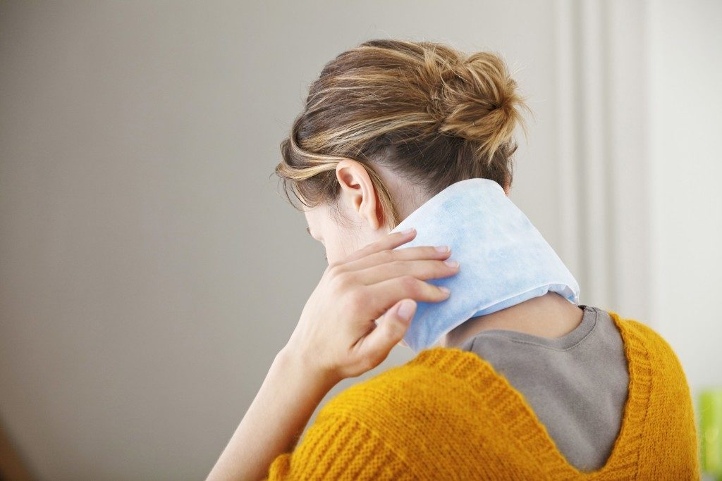 Woman putting ice pack in her neck