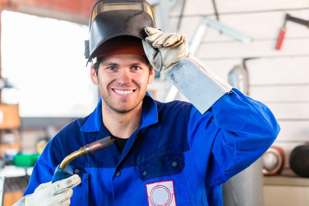 man uncovering welding helmet