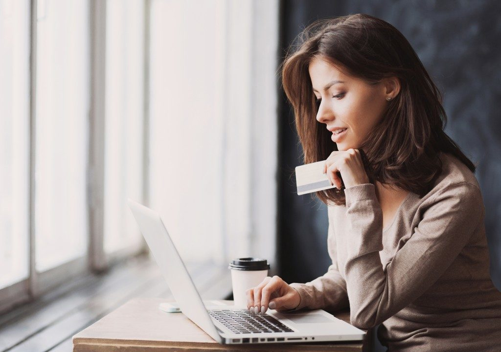 attractive woman paying using her credit card