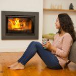 woman drinking coffee near her fireplace