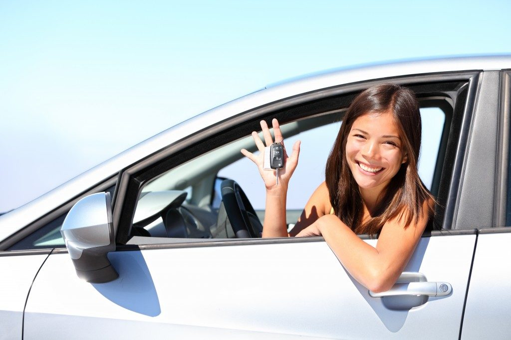 WOman holding car keys while riding inside the car