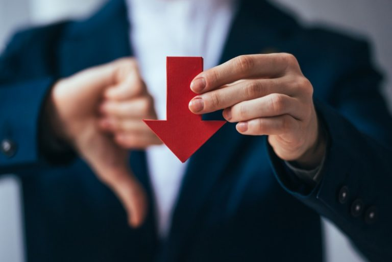 Businessman holding a red arrow pointing downwards symbolizing bankrupcy