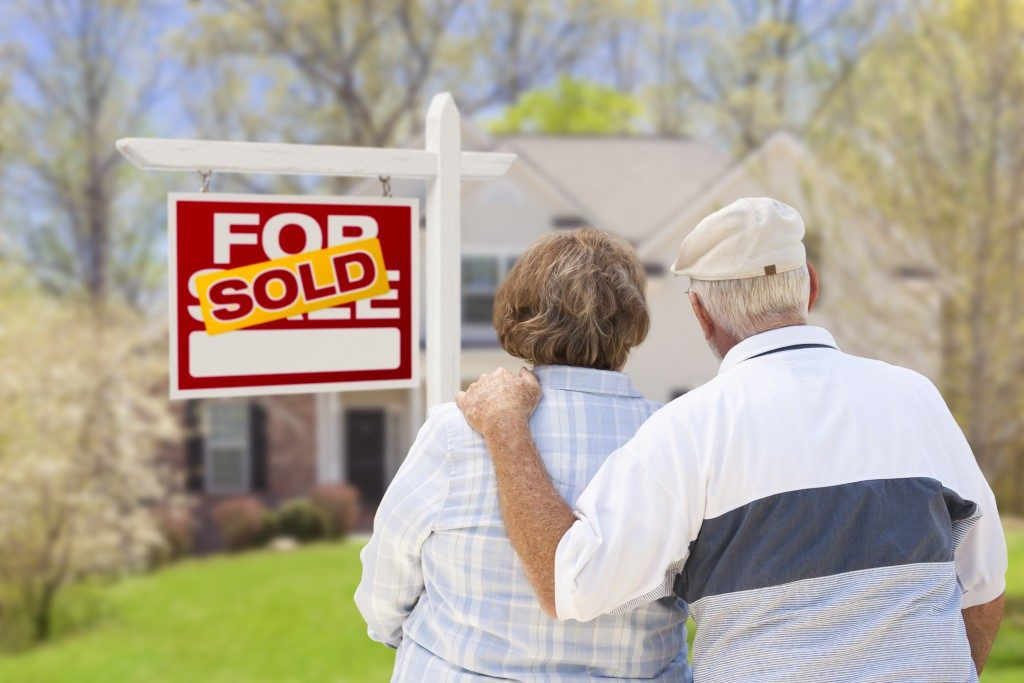 couple in front of sold real estate sign