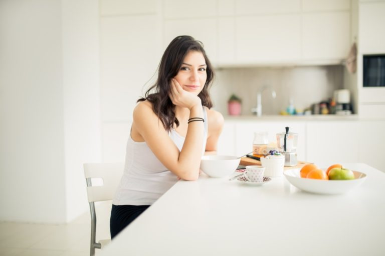 Young smiling woman eating cereal and smiling
