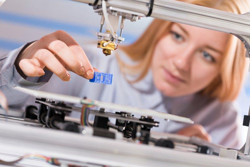 Woman using a 3D printer machine