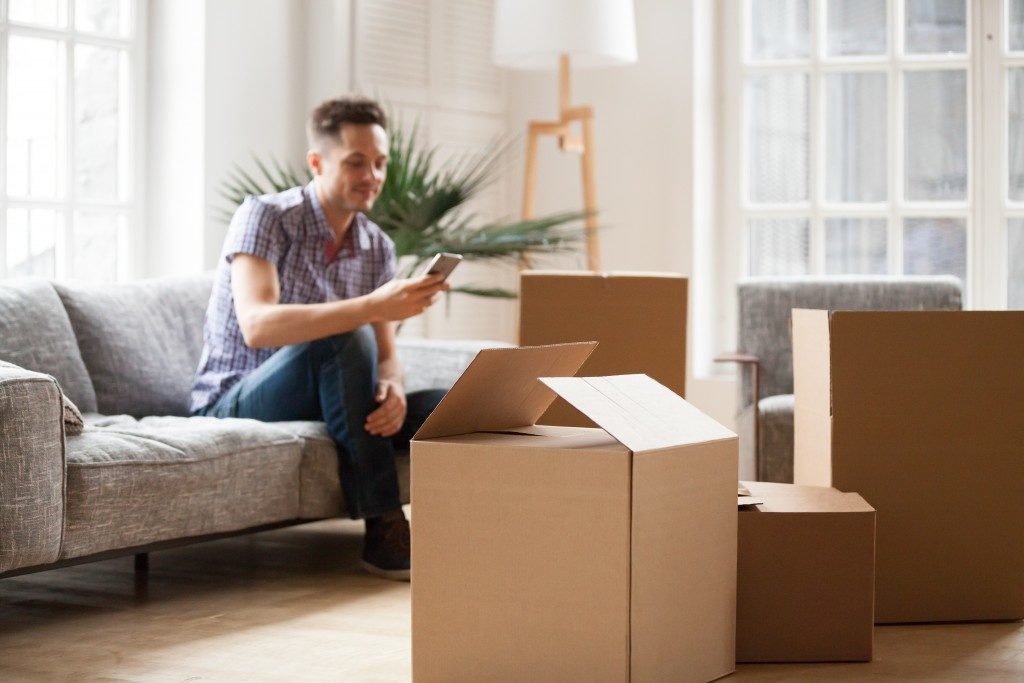 man seating on the couch surrounded by packaging boxes