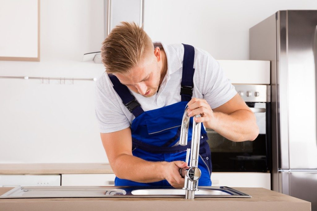 Plumber fixing the faucet in a house