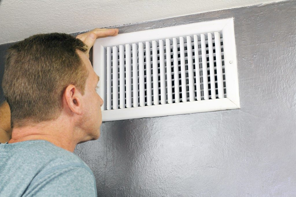 Man examining outflow air vent grid in home