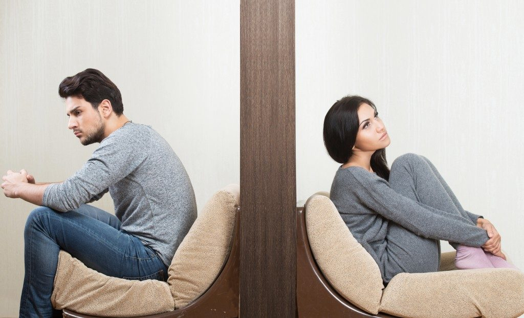 Conflict between man and woman sitting on either side of a wall