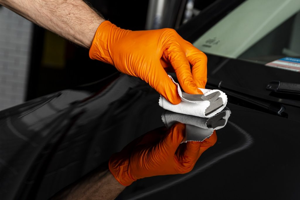 Car polish wax worker hands polishing car.