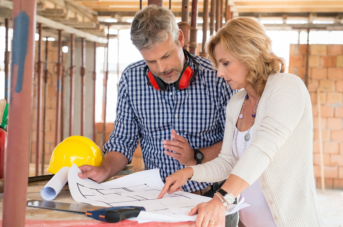 man and woman looking at house plans